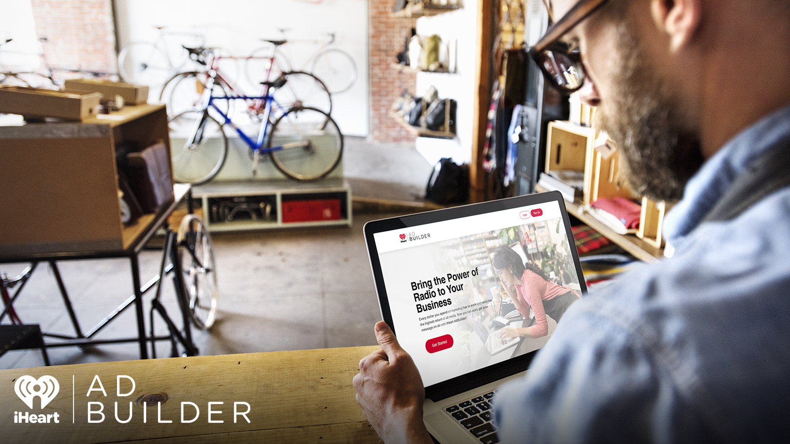Bike shop owner using iHeart AdBuilder on a laptop