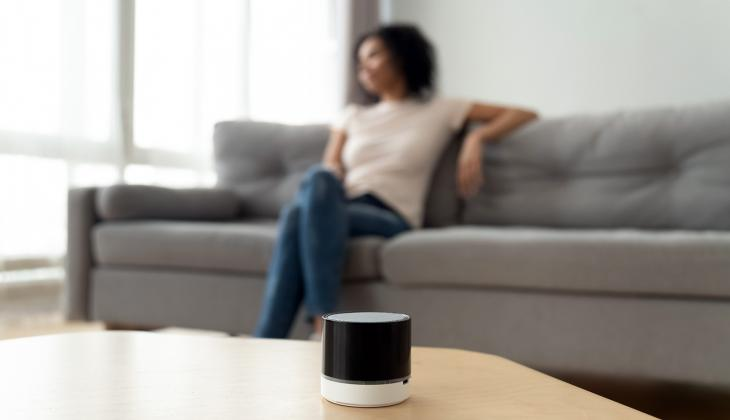 Woman listening to radio on a smart speaker at home