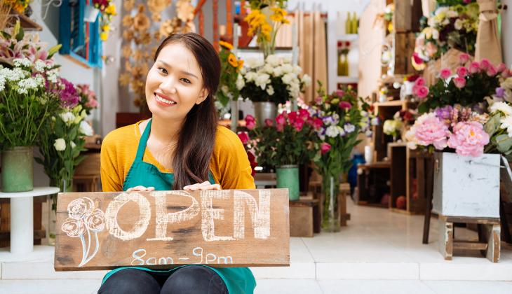 Flower shop owner holding an open sign