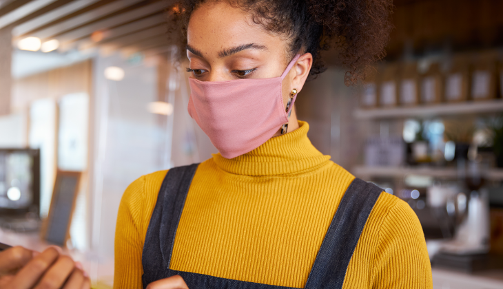 Small business owner wearing a face mask while working